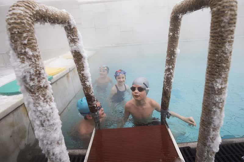 Дети купаются зимой в бассейне под открытым небом