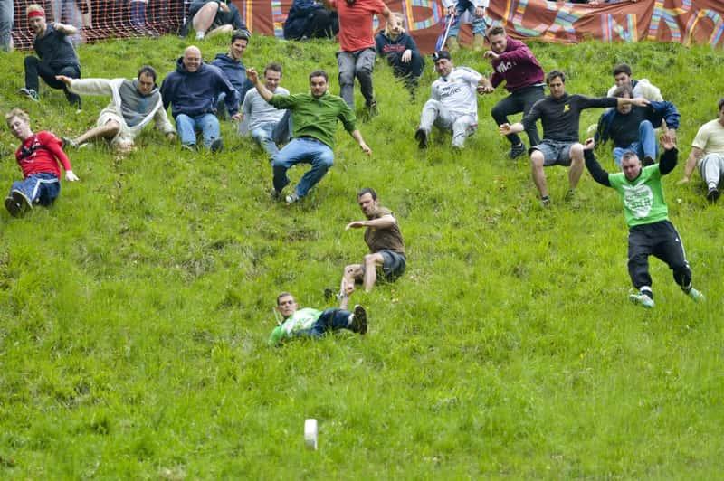 Сыр катится с горы на фестивале Купер Хилл